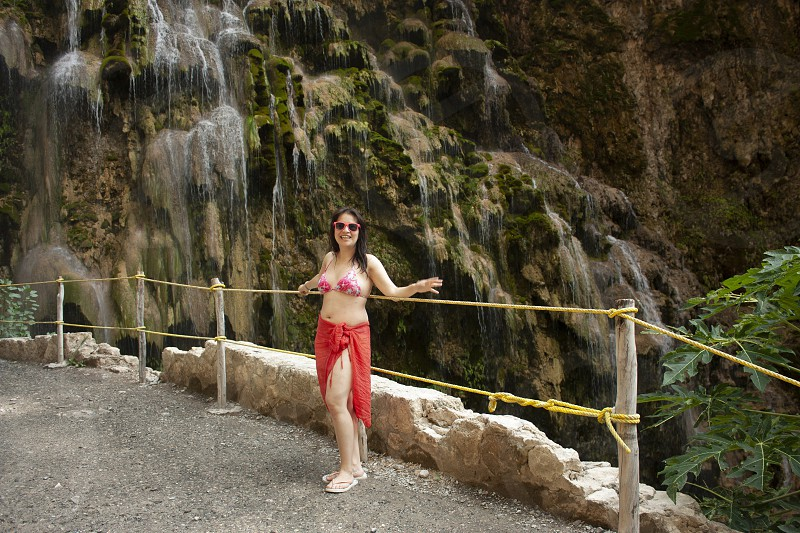 Woman wearing pink swimsuit sunglasses and pareo next to the green mossy rocks and water fall from the grotto of Tolantongo Hidalgo Mexico photo