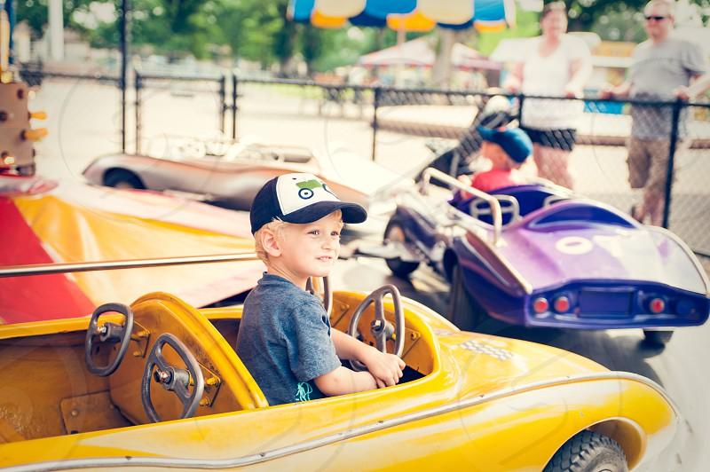 boy child youth ride park amusement park carnival fair race car car yellow steering wheel carousel around circles cap hat play fun summer happy joy purple yellow blue drive driving photo