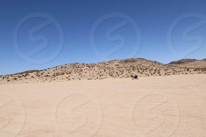Desert landscape with two tiny bike riders in the far distance photo