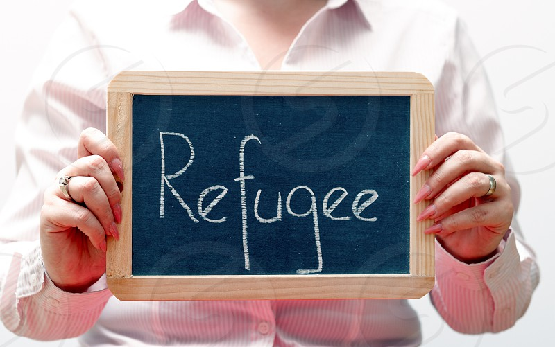 Refugee word written with chalk on a blackboard photo