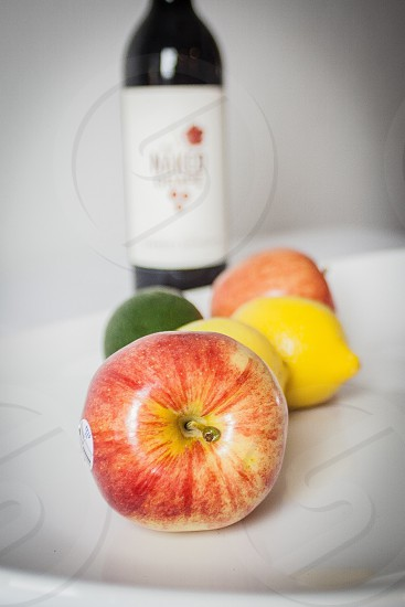 red apple near bottle with white label photo