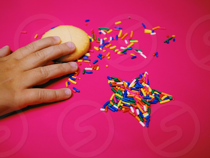 person holding cookie with candy sprinkles photo