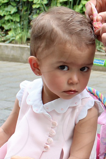 Little girl looking at the camera with a concerned expression on her face. photo