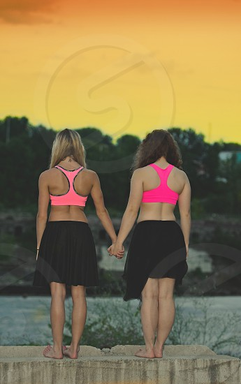 Two teen girls / friends holding hands at dusk looking out at the river. photo
