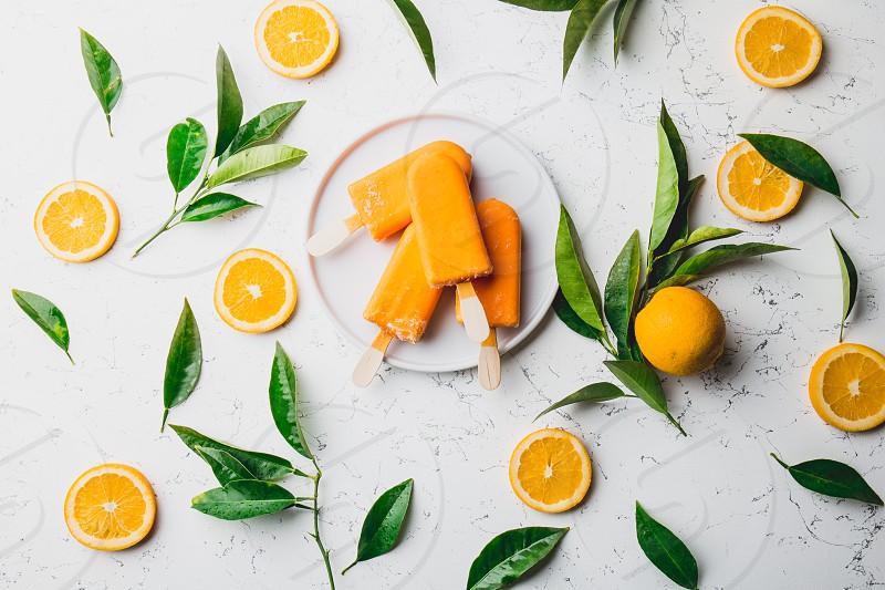 Homemade orange ice cream on stick. white background with orange fruits slices and orange tree leaves. photo