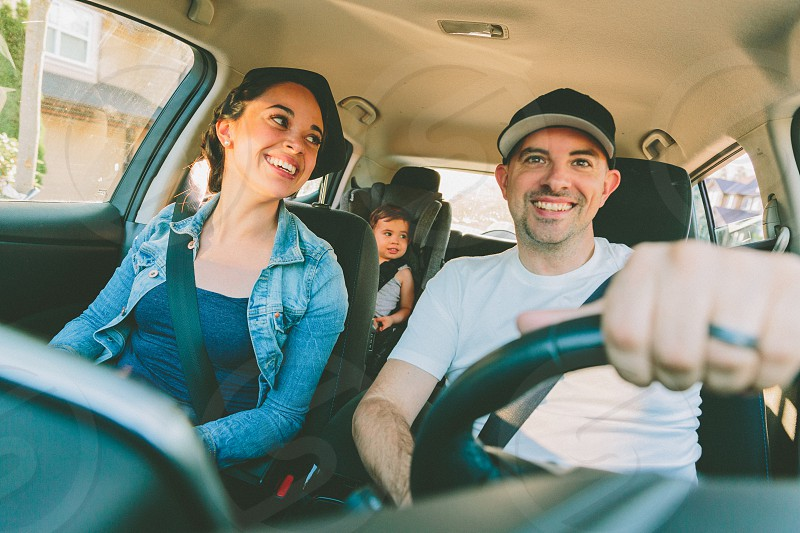 A family of three inside their car as they drive.  photo