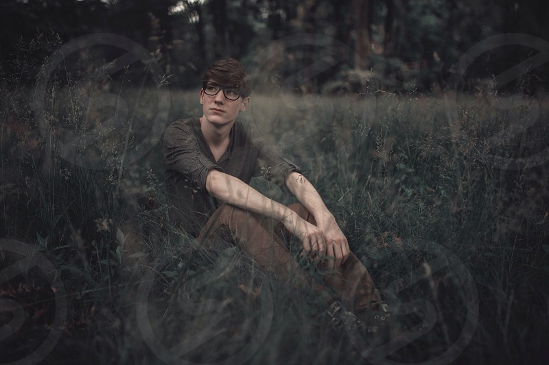 man in dark free shirt brown pants with glasses sitting in a grass field photo