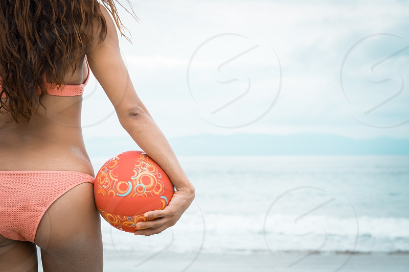 Woman beach fitness - back side of attractive female holding beach volleyball Riviera Nayarit Mexico photo