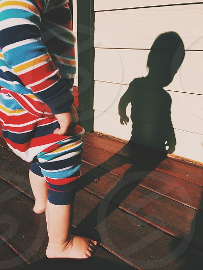 child wearing red blue and yellow striped pajamas standing on a wood deck of a white house in the sun with shadow reflection photo