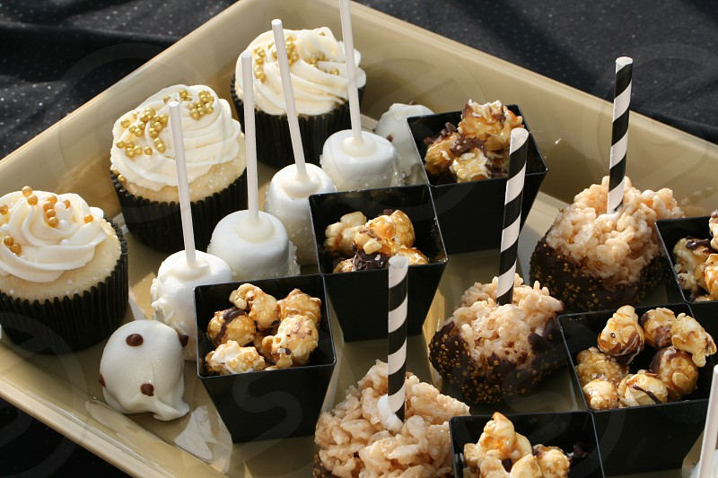 Snacks and dessert tray with cupcakes marshmallows dipped in chocolate rice krispie treats popcorn photo