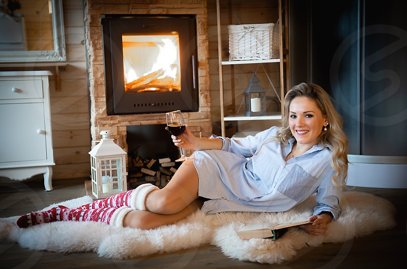 Young adult beautiful woman with red wine glass relaxing in rustic  mountain cabin photo