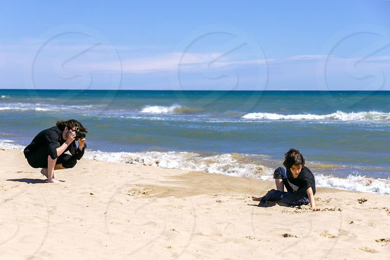 Professional photographer with photo camera shooting teenage boy lying on sandy beach of ocean coast photo