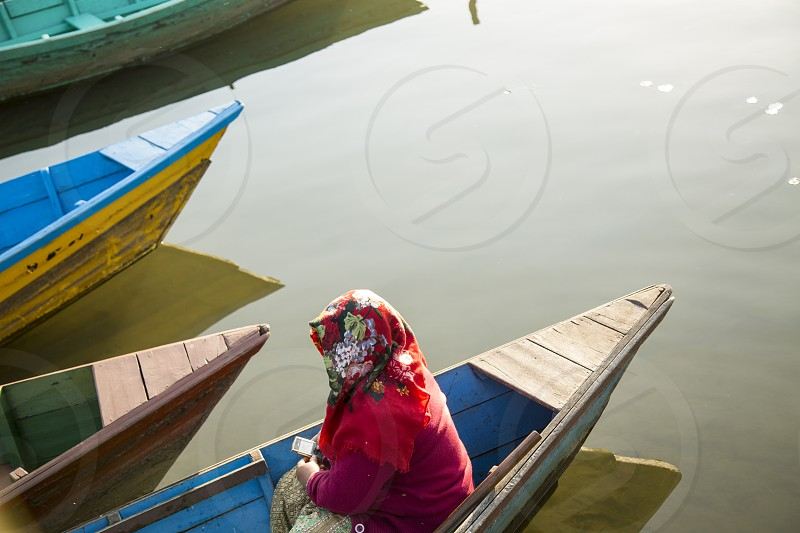 Nepali woman waiting in boat at Phewa Lake in Pokhora Nepal. photo