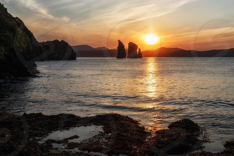 Beautiful Kamchatka Peninsula seascape: view of sunset over Three Brothers Rocks in Avacha Bay (Pacific Ocean). Kamchatka Region Russian Far East Eurasia. photo