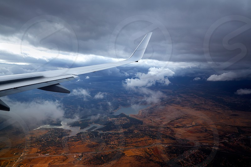 Aircraft wing in a cloudy stormy clouds sky flying photo