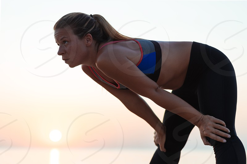 Young woman catching a breath after a run on the beach photo