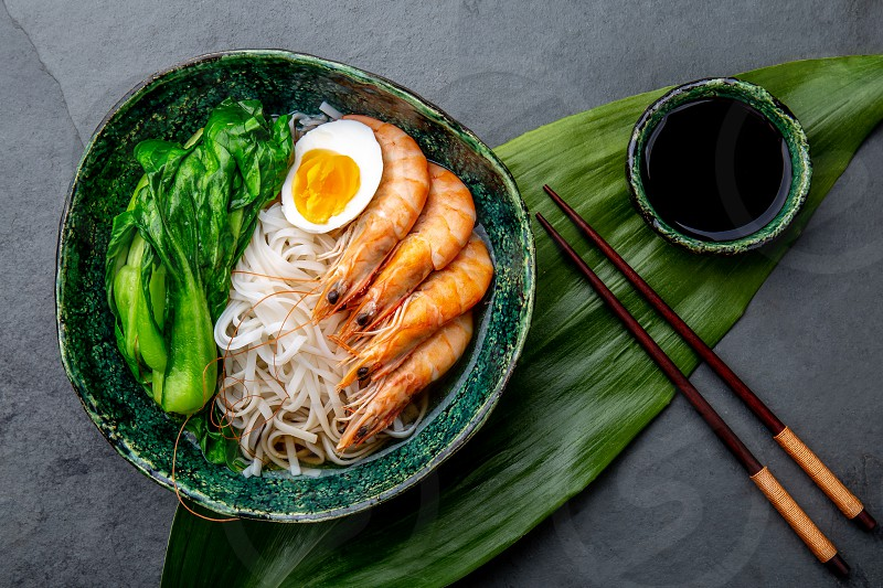 Rice noodles with Shrimps Egg Pok choy cabbage in green bowl gray background. Top view. photo