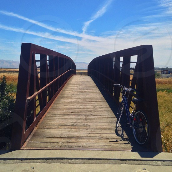 clear bridge pathway view with bicycle beside it photo