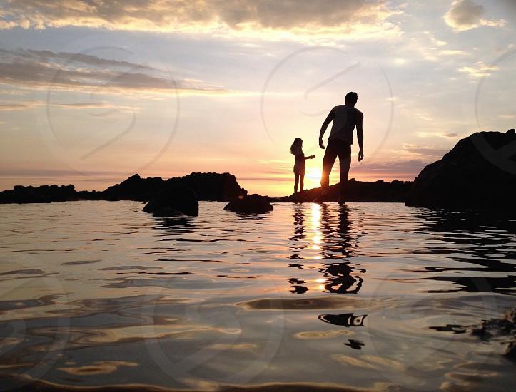 man with girl standing on rock near seashore photo
