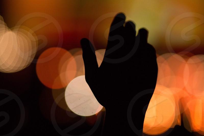 Worshipful hand with defocussed orange background stage light photo