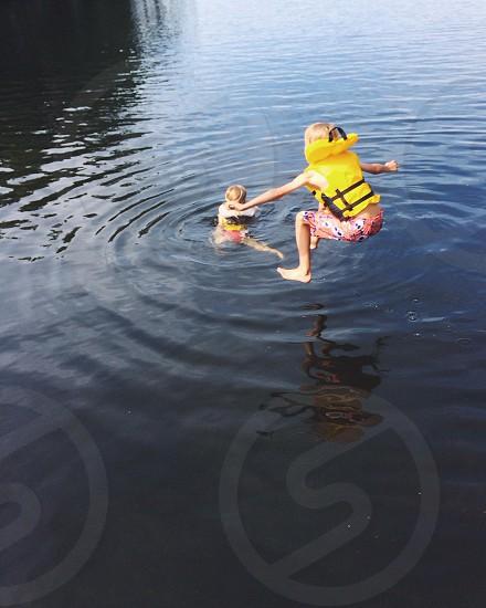girl jumping on lake photo