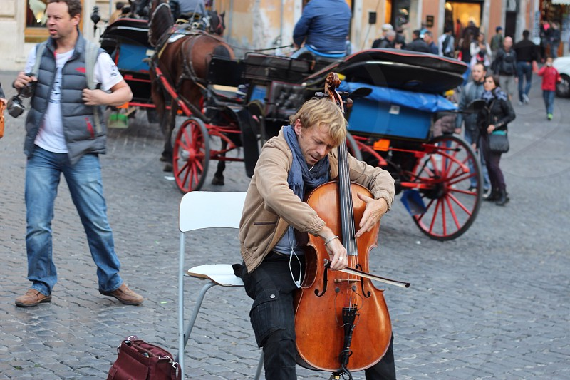 man in brown jacket and black pants using brown cello photo