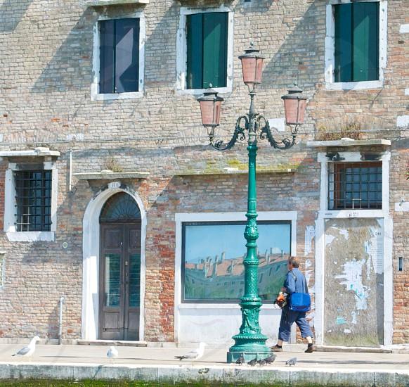 person in blue bag walking near green street pole light photo