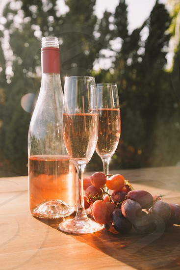 two champagne flutes filled with rose wine on a table next to the wine bottle and purple table grapes with trees in the distance photo