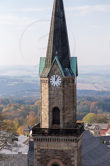 The church tower of Schöneck on a sunny day. It is 5 after 12 o'clock. photo
