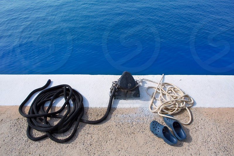 Boat noray marine rope and shoes in marina port photo