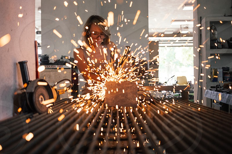 sparks flying from a woman cutting a piece of wood photo