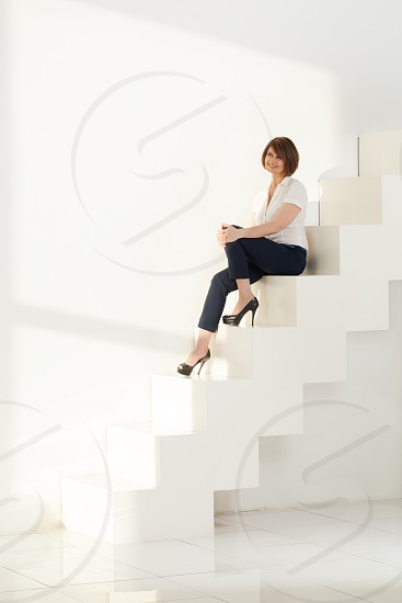 Smiling businesswoman sitting on steps of modern ladder photo