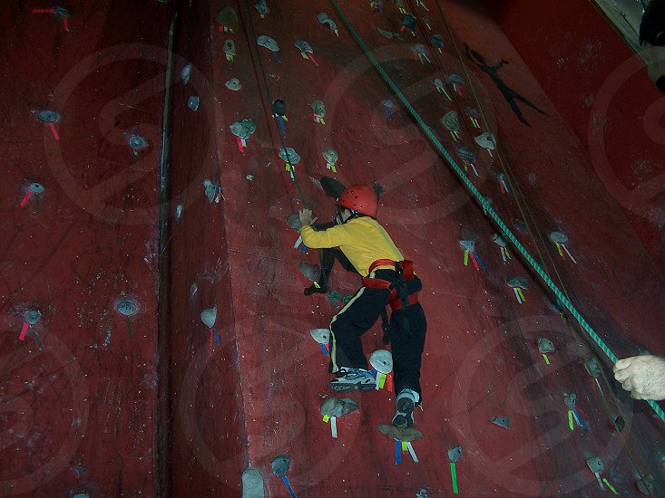 person climbing on wall wearing a red helmet photo