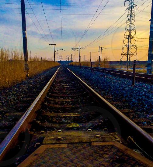 railroad near transmission tower between grass field photo