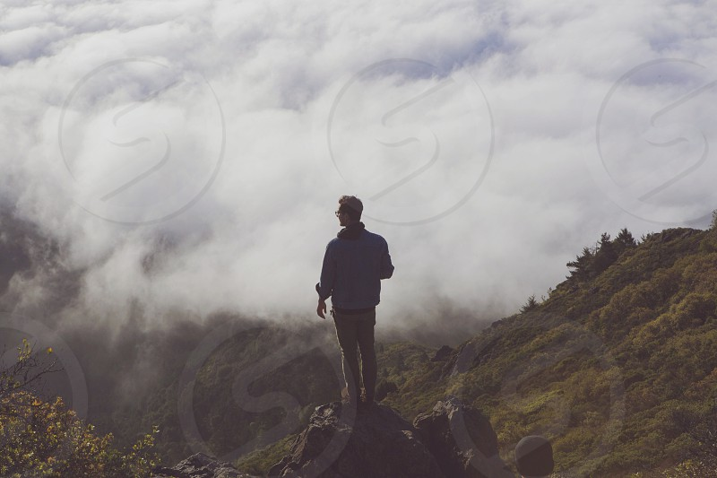 man standing on rock facing white clouds photo