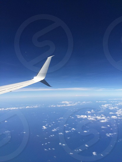 aircraft with silver wing and winglet on flight over white clouds and sea photo