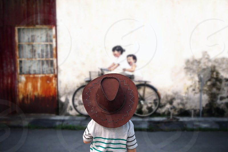 boy in white t shirt wearing cowboy hat looking at girl and boy riding bicycle wall art during daytime photo