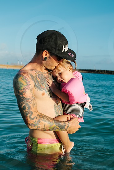 man with tattoos wearing a printed black ball cap holding a little girl wearing pink floaties standing in water photo