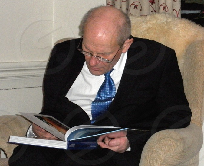 man in black and coat and blue neck tie reading while sitting photo
