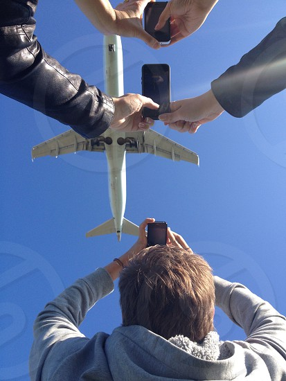 people taking picture of white airplane photo