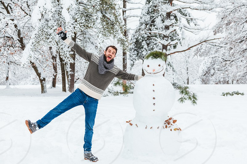 Young man making snowman in the park photo