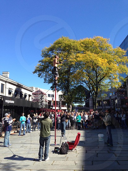 people watching on man performing on street photo