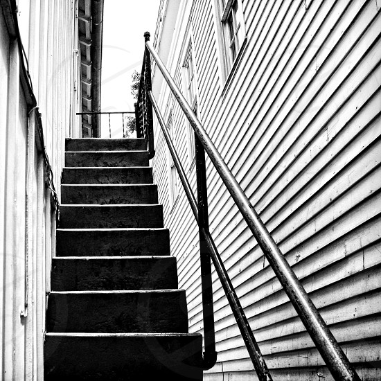 A black and white image of stairs against a wall. Lines of the steps and wall boards are perpendicular to each other. photo