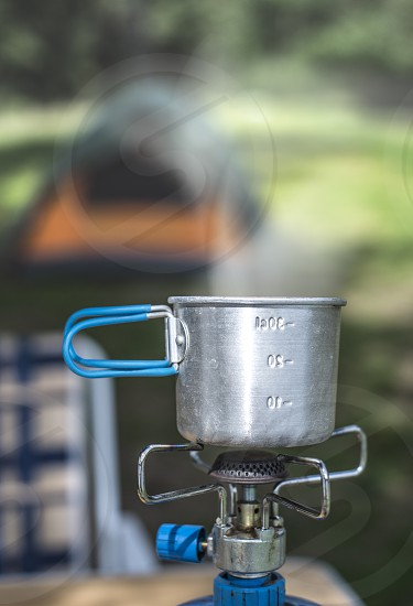 Tourist cup on gas stove in the forest. Tent on background. photo
