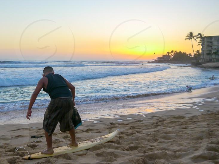 Makaha sunset boy stand on a surf board laying on the sand Hawaii Oahu island photo