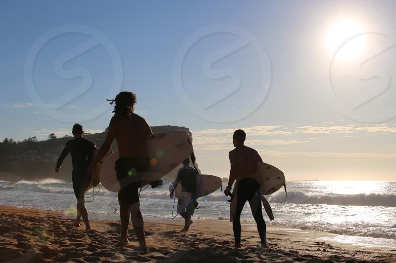 Lens flare surfers beach photo