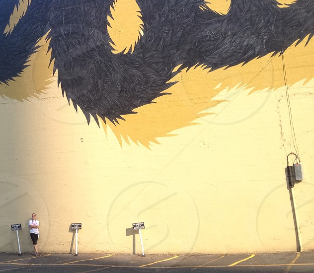 woman in white t shirt leaning by the yellow and black dragon painted wall photo