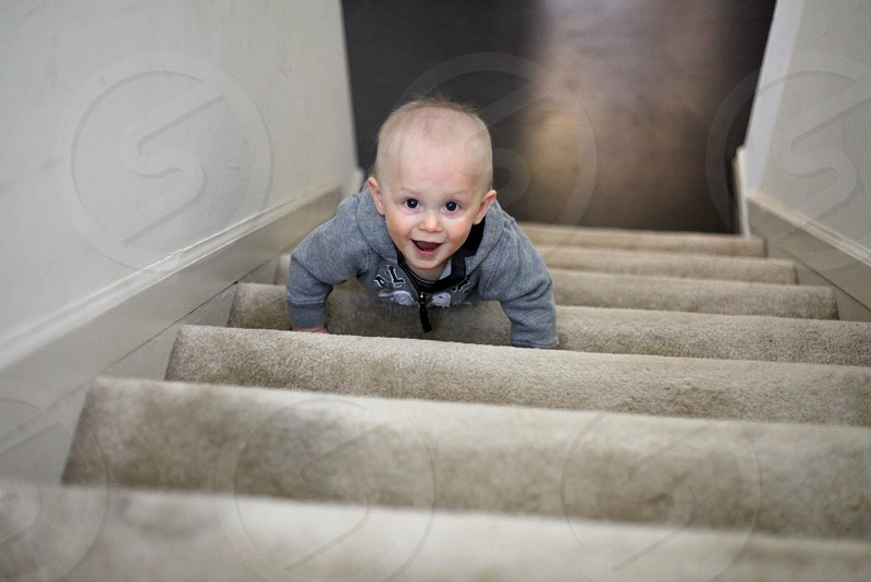 boy in grey zippered hoodie on stairs photo