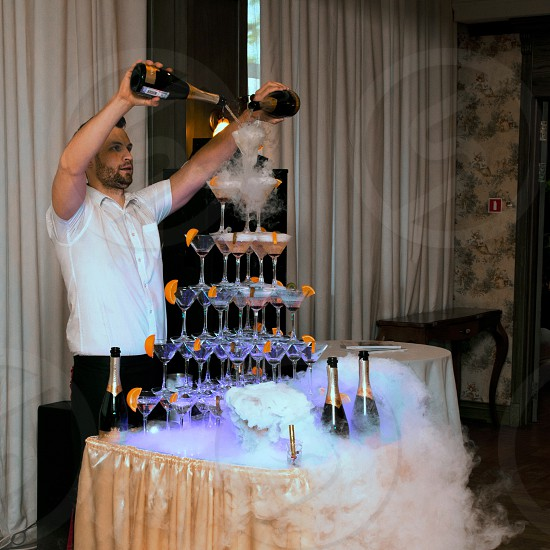man holding two champagne bottles while pouring champagne on top of martini glasses photo