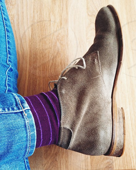 Suede shoes with purple socks on wooden flooring photo